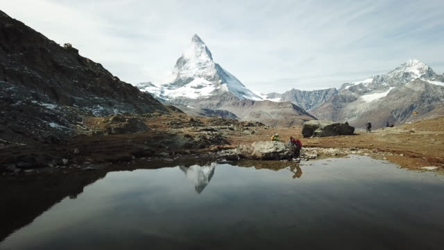 mountain bikers take break on alpine lake below matterhorn - schweiz stock-videos und b-roll-filmmaterial