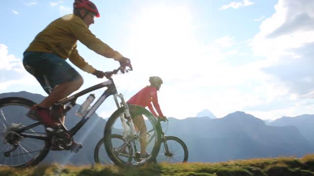 mountain bikers traverse high mtn ridge towards tent camp - マウンテンバイク点の映像素材/bロール