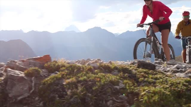 mountain bikers traverse high mtn ridge - mountainbike stock-videos und b-roll-filmmaterial