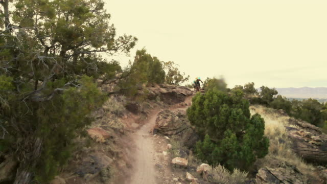 mountain biking adult female in western colorado desert arid climate late evening 4k video - steep hill stock videos & royalty-free footage
