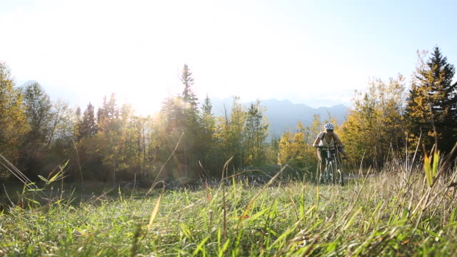 Mountain biking couple ascend grass ridge in autumn, mountains