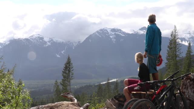 mountain biking couple climb look off from high viewpoint - mountain biking stock videos & royalty-free footage