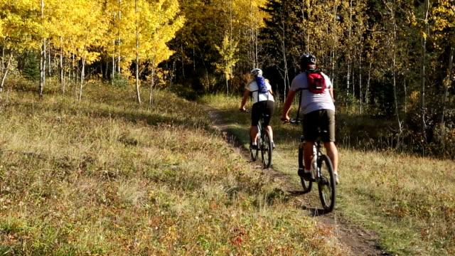 Mountain biking couple descends trail into autumn forest