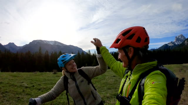 mountain biking couple exchange high fives on top of meadow track - enjoyment stock videos & royalty-free footage