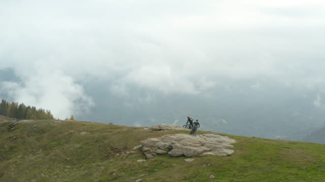 mountain biking couple explore lush mountain hilltop - in den fünfzigern stock-videos und b-roll-filmmaterial
