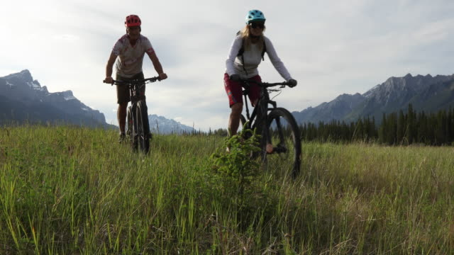 vidéos et rushes de couples de vélo de montagne suivent le chemin par le pré - 60 64 ans