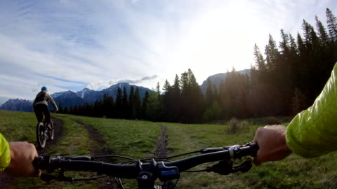 mountain biking couple follow track through meadow, past fork - footpath stock videos & royalty-free footage