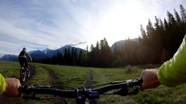 mountain biking couple follow track through meadow, past fork - environment stock videos & royalty-free footage