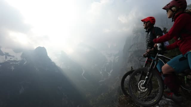 Mountain biking couple pause at edge of precipice, looking off