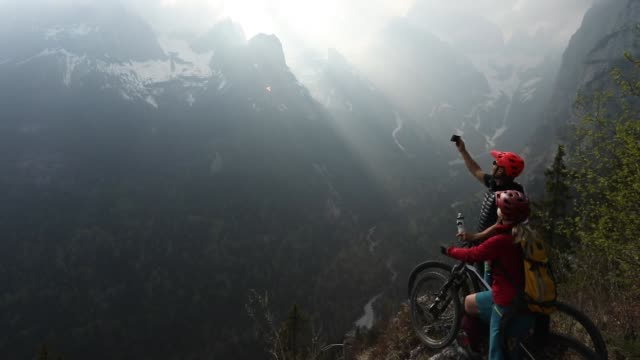 mountain biking couple pause at edge of precipice, looking off - portability stock videos and b-roll footage