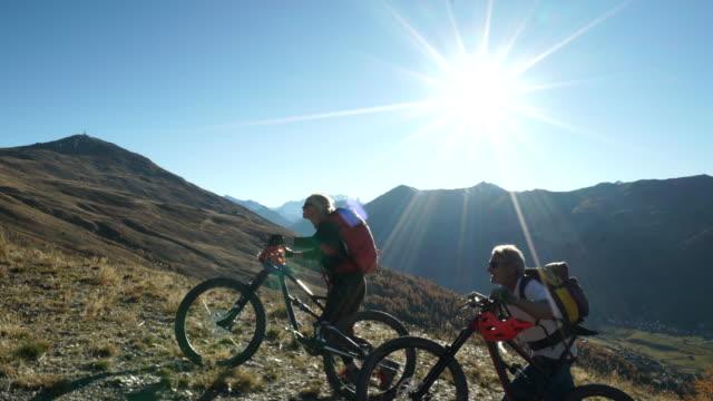 Mountain biking couple, ride bikes up to mountain viewpoint