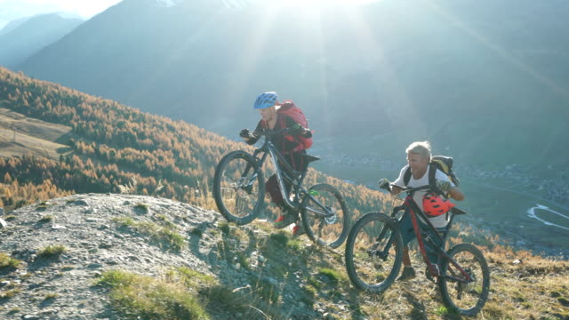 mountain biking couple, ride bikes up to mountain viewpoint - mature adult stock videos & royalty-free footage