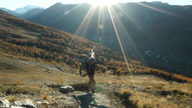 mountain biking couple, ride bikes up to mountain viewpoint - scena rurale video stock e b–roll
