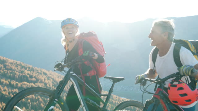 mountain biking couple, ride bikes up to mountain viewpoint - 熟年カップル点の映像素材/bロール