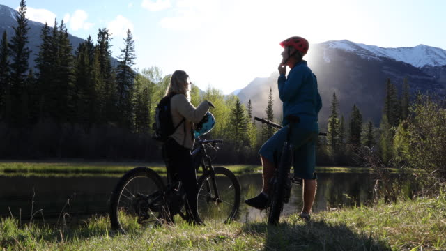mountain biking couple ride to creek edge, below mountains - leggings stock videos & royalty-free footage