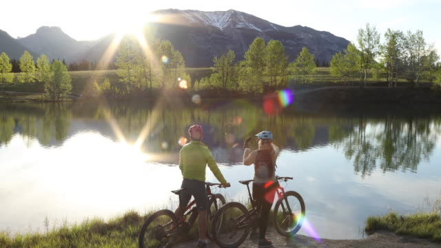 mountain biking couple ride to lake edge, below mountains - photography themes stock videos & royalty-free footage