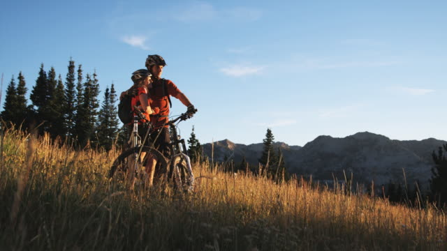 mountain biking couple - motorradfahrer stock-videos und b-roll-filmmaterial