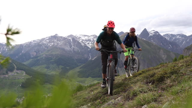 mountain biking friends venture across alpine meadow - mountain biking stock videos & royalty-free footage