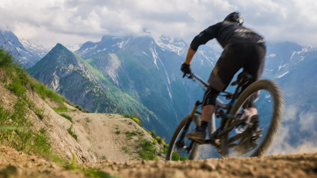 mountain biking in mountain terrain, jumping - andare in mountain bike video stock e b–roll