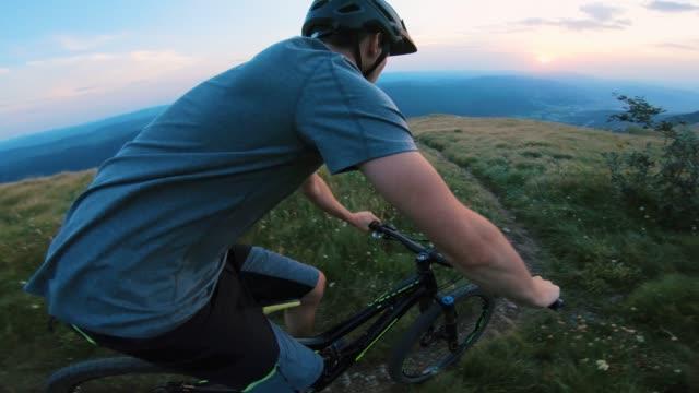 vídeos de stock e filmes b-roll de mountain biking on grassy landscape in mountains at sunset - cavalgada de lazer