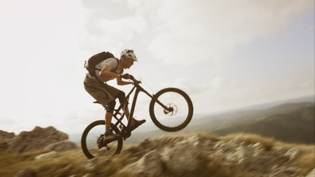 vídeos de stock, filmes e b-roll de ts slo mo mountain bike no rocky top - mountain bike bicicleta