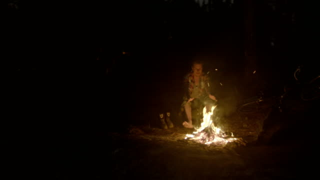 mountain camp with bonfire. man warming up after hike. drone point of view - camp fire stock videos and b-roll footage