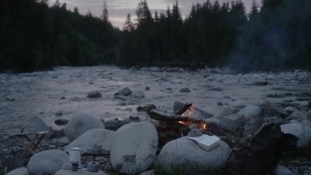 mountainbike-camp mit lagerfeuer. fluss im hintergrund - lagerfeuer stock-videos und b-roll-filmmaterial