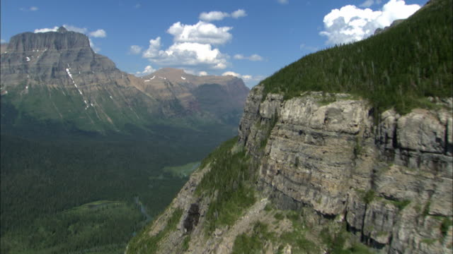 Mountain cliffs rise above a green valley in Glacier National Park, Montana.