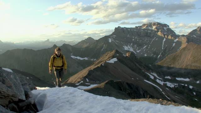 vidéos et rushes de ws, pan, mountain climber ascending mountain, banff national park, alberta, canada - seulement des hommes d'âge mûr