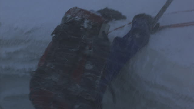 A mountain climber at the edge of a snowy ridge is struggling to climb over it.
