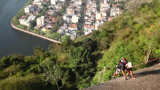 vídeos de stock, filmes e b-roll de ws mountain climber climbing sugar loaf urca neighborhood / rio de janeiro, brazil - esportes extremos