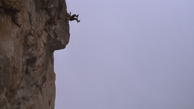 stockvideo's en b-roll-footage met a mountain climber in tibet drops over a rock wall on his rope, bounces off the wall and swings freely. - schommelen bungelen