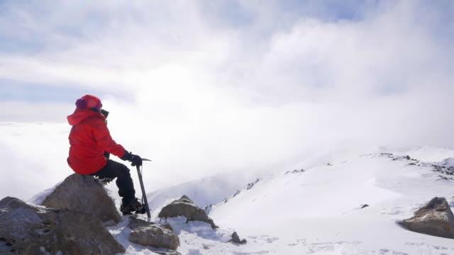vídeos y material grabado en eventos de stock de trepador de la montaña está mirando el hermoso paisaje en la cima de la montaña en invierno - accesorio de cabeza