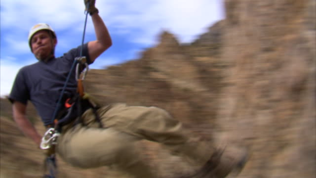 ms pan mountain climber jumping over camera / provo, utah, usa - abseiling stock videos & royalty-free footage