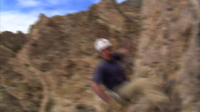 vídeos de stock e filmes b-roll de ms pan mountain climber jumping over camera / provo, utah, usa - provo