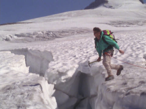 mountain climber jumping over crevice in snow - crevice stock videos & royalty-free footage