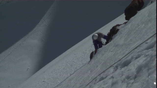a mountain climber moves sideways on a snowy mountain. - safety harness stock videos & royalty-free footage