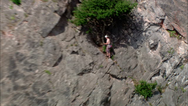 A mountain climber scales a cliff on the southwest coast of England. Available in HD.