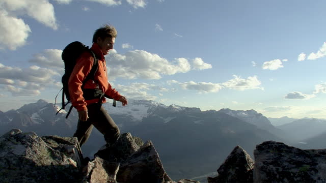WS, PAN, mountain climber walking across and standing on mountain summit, Banff National Park, Alberta, Canada