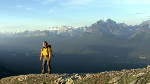 WS, mountain climber walking across mountain ridge and stopping to look at view, Banff National Park, Alberta, Canada