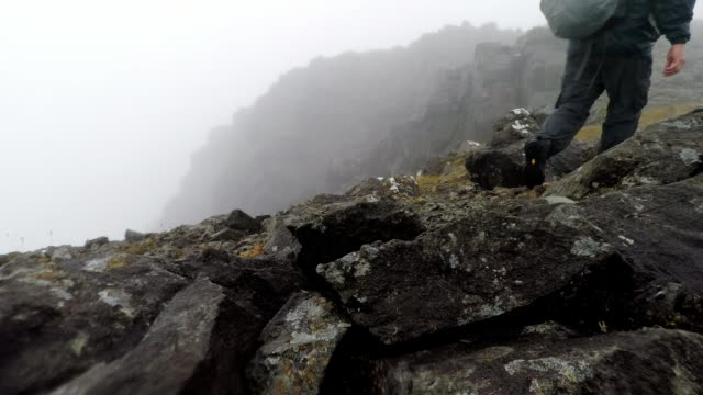 mountain climber walking across rocky and rainy mountain landscape, scotland - extreme weather stock videos & royalty-free footage
