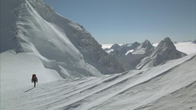 a mountain climber walks up a snow covered slope. - 冠雪点の映像素材/bロール