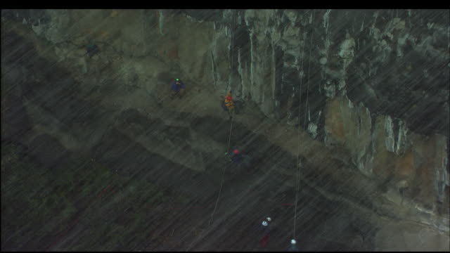 mountain climbers rapidly descend a cliff face during a snowstorm. - abseiling stock videos & royalty-free footage