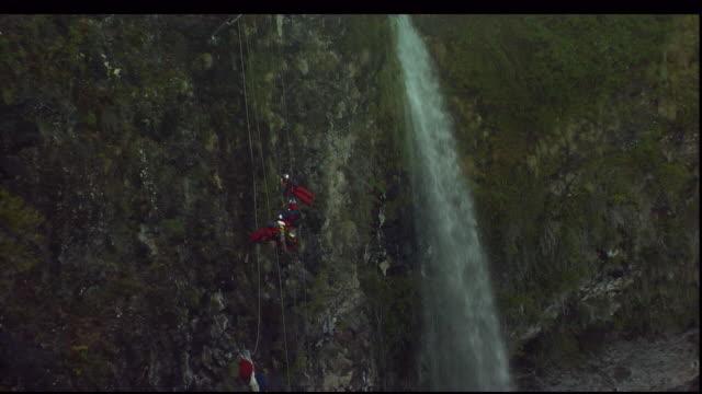 vidéos et rushes de mountain climbers rappel down a cliff near a waterfall. - chute d'eau
