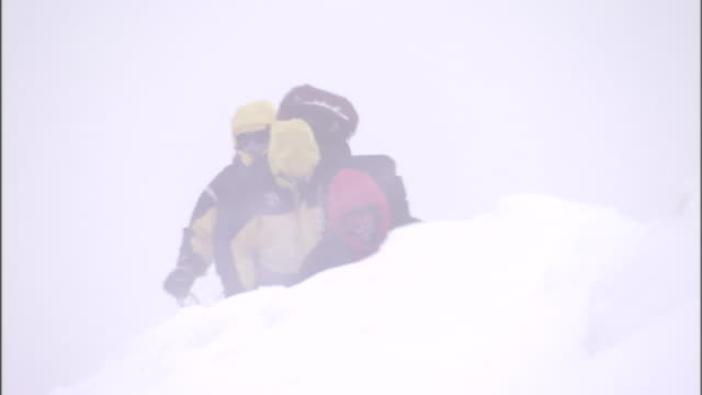 mountain climbers struggle through drifted snow and blizzard conditions. - deep snow stock videos & royalty-free footage