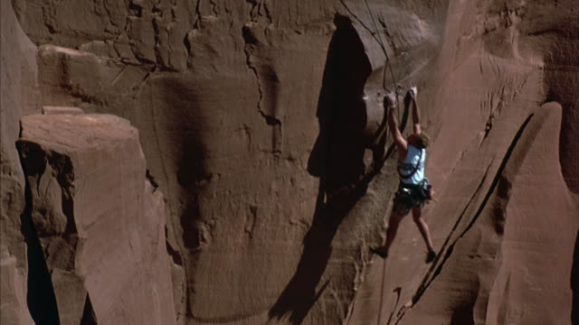 a mountain climbers swinging from a ledge before scaling a steep rock face. - felswand stock-videos und b-roll-filmmaterial
