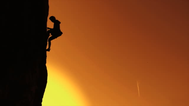 stockvideo's en b-roll-footage met hd slow-motion: mountain climbing at sunset - rotsklimmen
