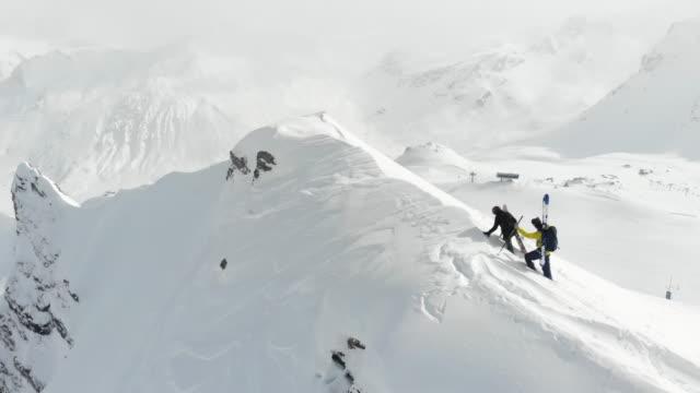 mountain climbing skiers clear skies - sci e snowboard video stock e b–roll