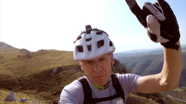 Mountain cyclist making funny selfies on the mountain top