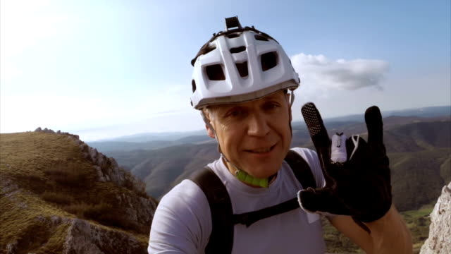 Mountain cyclist showing the landscape while on video call